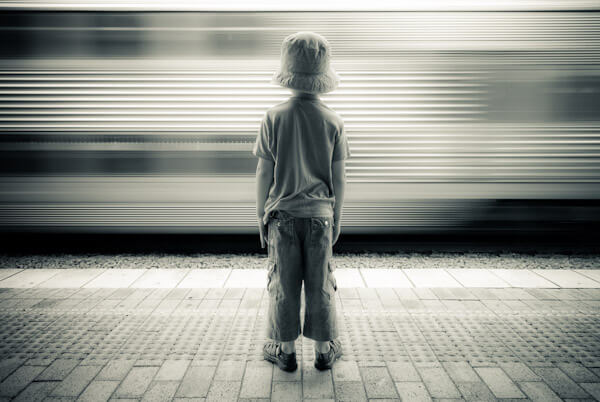boy standing in front of train passing a station at speed