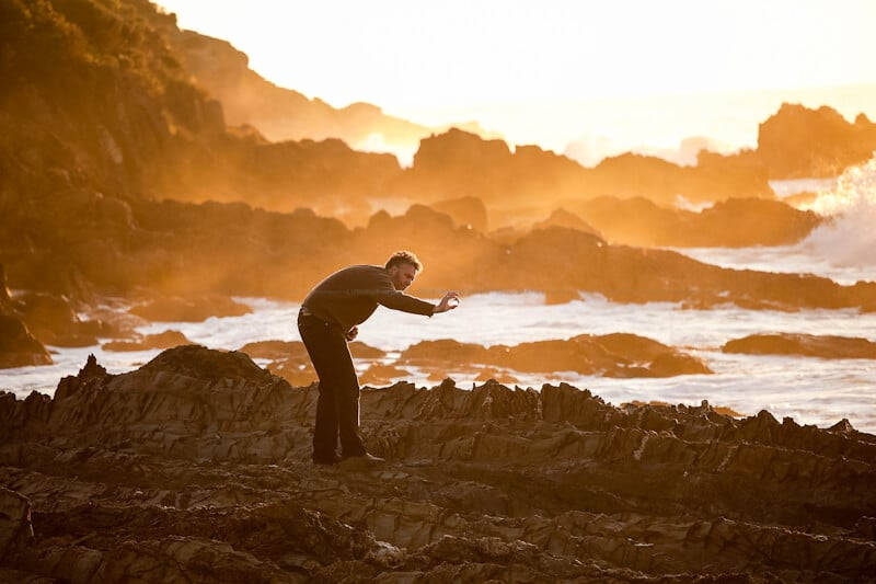 Figure of a man searching rocky wave platform bathed in golden dawn light