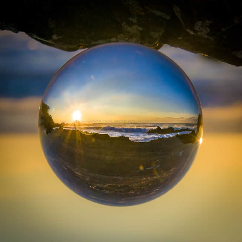 a coastal sunrise through a glass sphere
