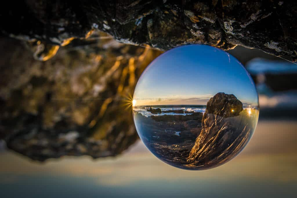 Rockt coast at dawn seen refracted through a glass sphere