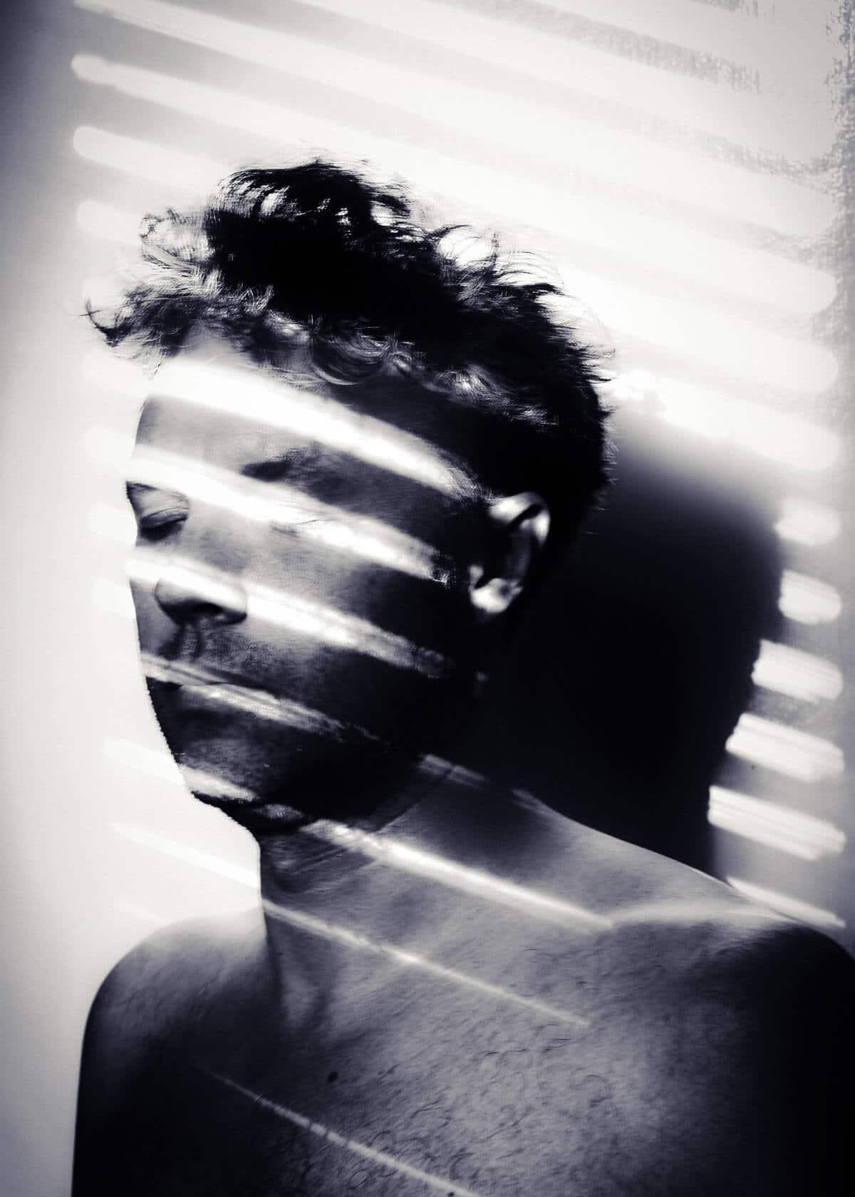 Monochrome self portrait with white light bars across my face