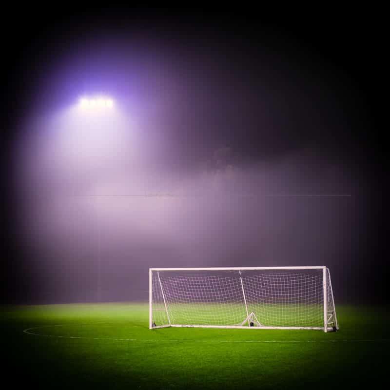 Goal lit by misty lights on green